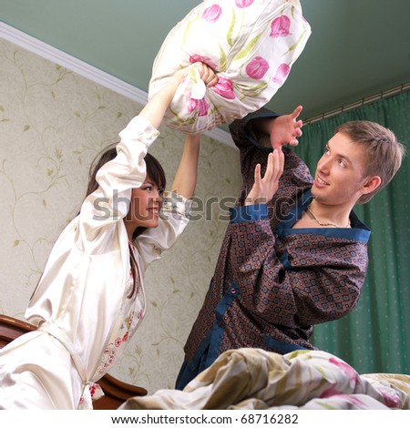 Cheerful young couple having a pillow fight in bed - stock photo