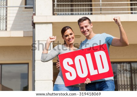 cheerful young couple holding sold sign in front of their old house - stock photo