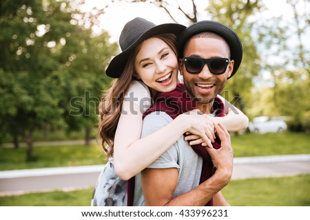 Cheerful young couple hugging and laughing in park