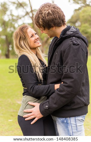 Cheerful young couple hugging and smiling in a park - stock photo
