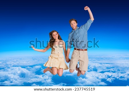 Cheerful young couple jumping against blue sky over clouds at high altitude - stock photo