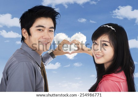 Cheerful young couple looking at the camera while forming heart symbol with their hands - stock photo