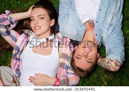 Cheerful young couple lying on a grass in a park  - stock photo