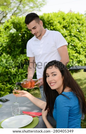 cheerful young couple man and woman cheering with a glass of wine outdoor in a summer barbecue garden party - stock photo