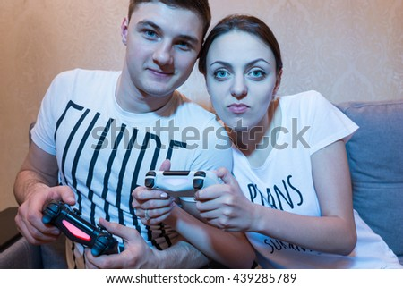 Cheerful young couple of boy and girl playing video game sitting on the sofa in front of TV at home in a relaxed atmosphere - stock photo