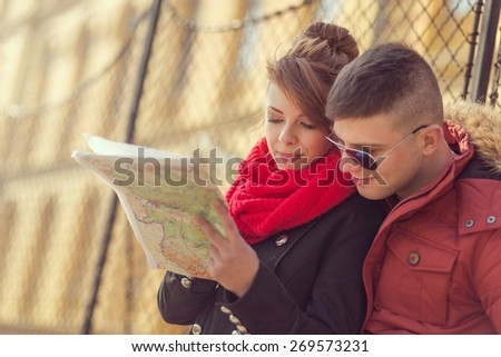 Cheerful young couple on a vacation sightseeing and reading a map - stock photo