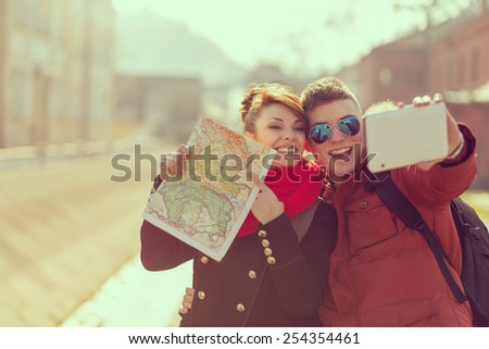 Cheerful young couple on a vacation sightseeing and taking a selfie - stock photo