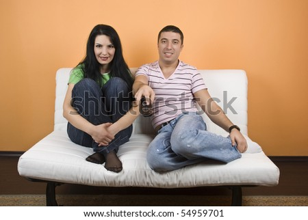 Cheerful young couple on white sofa watching TV - stock photo
