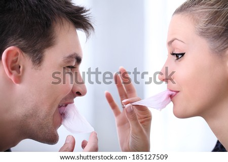 cheerful young couple playing with chewing gum