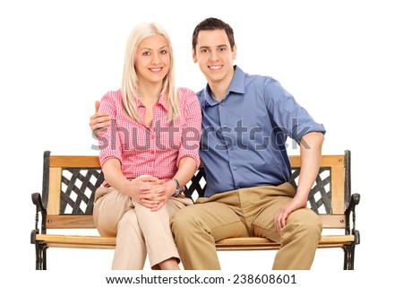 Cheerful young couple posing seated on a bench isolated on white background - stock photo