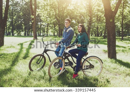 Cheerful young couple riding a retro bike and smiles. Young lovers couple ride a bike outdoors - stock photo