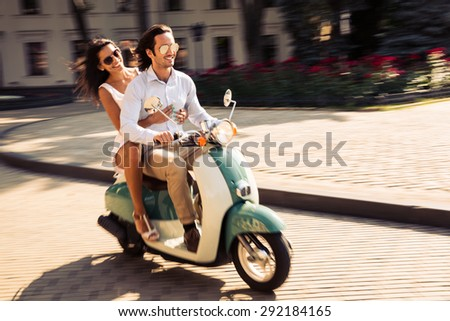 Cheerful young couple riding a scooter in town with fun - stock photo