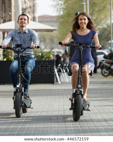 Cheerful young couple riding on electric bikes in the city street . Focus on man - stock photo