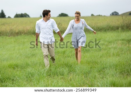 cheerful young couple running in countryside - stock photo