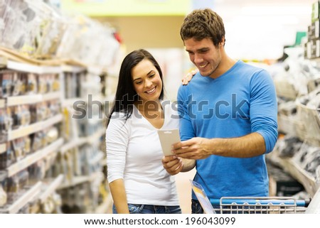 cheerful young couple shopping in hardware store - stock photo