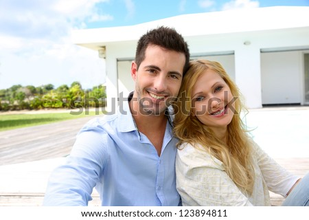 Cheerful young couple sitting in front of modern house - stock photo