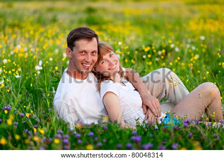 cheerful young couple sitting on  green lawn. man embraces a woman. grass is blurred in the background