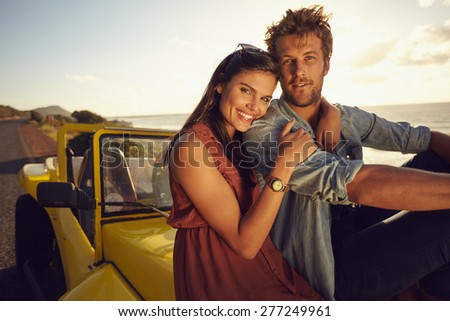 Cheerful young couple sitting on the hood of their car while out on a roadtrip. Beautiful young couple together on a holiday, outdoors. - stock photo