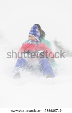 Cheerful young couple sledding in snow - stock photo