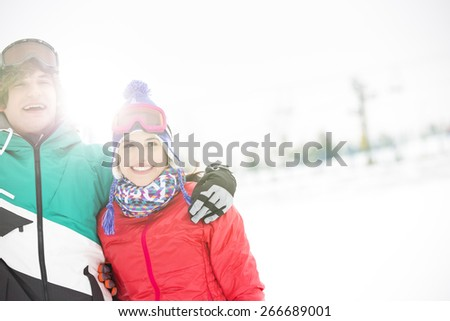 Cheerful young couple standing arm around in snow - stock photo
