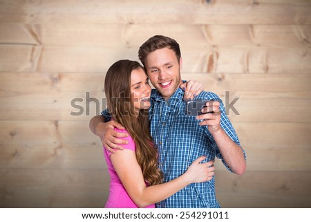 Cheerful young couple taking selfie with smart phone against bleached wooden planks background - stock photo