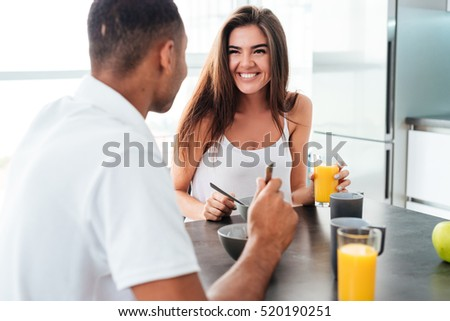 Cheerful young couple talking and having breakfast together at home