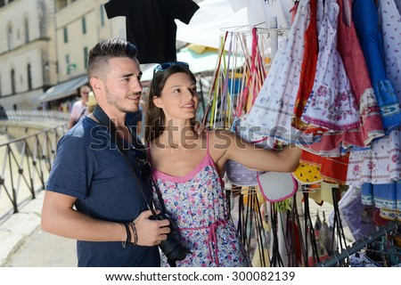 cheerful young couple visiting europe buying at souvenir shop - stock photo