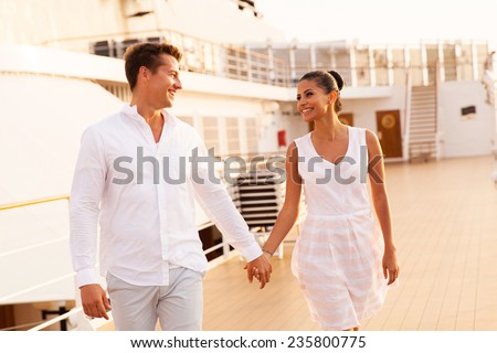 cheerful young couple walking on cruise ship - stock photo