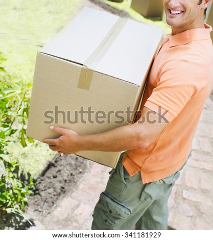 Cheerful young delivery man holding a cardboard box - stock photo