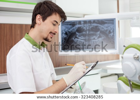 Cheerful young dental doctor is working in laboratory. He is holding a folder of document and writing. The man is sitting near x-ray of human jaw on screen. He is smiling - stock photo