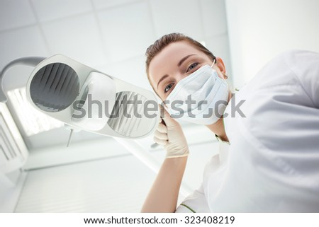 Cheerful young dentist is treating her patient. She is standing and looking down with joy. The woman is touching equipment is laboratory. She is wearing mask - stock photo