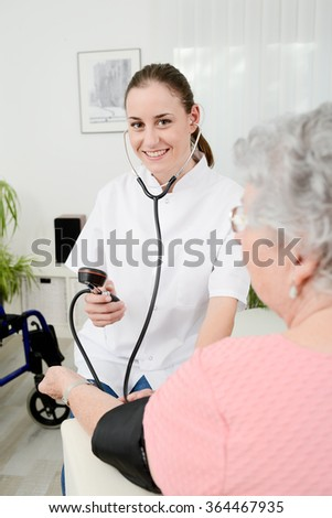 cheerful young doctor giving medical health care to elderly woman at home - stock photo