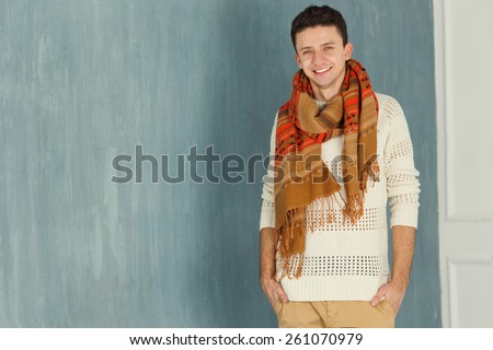 Cheerful young European man looking at camera. Portrait of a smile young man standing with against gray background. Handsome caucasian man smiling. Male model. Copy space. Friendly face. - stock photo