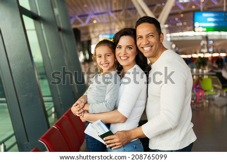 cheerful young family at airport waiting for their flight - stock photo