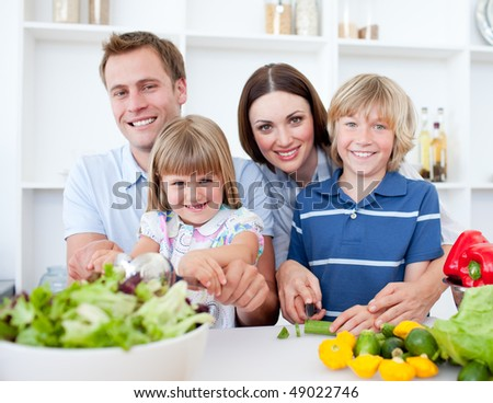 Cheerful young family cooking together in the kitchen - stock photo