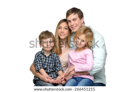 Cheerful young family of four posing and looking at camera. Isolated on white background. Concept for happy family - stock photo