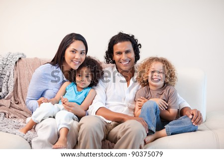 Cheerful young family sitting on the sofa together