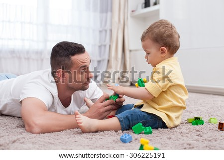 Cheerful young father is playing with his son on flooring. He is giving him a toy and looking at him with love. The child is taking a plaything with joy - stock photo