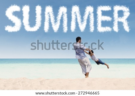 Cheerful young father twist his son on the tropical shore under a summer's cloud - stock photo