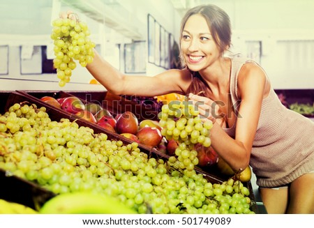 Cheerful young female customer holding ripe bunch of grapes on fruit market