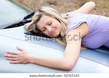 Cheerful young female driver hugging her new car - stock photo