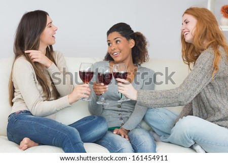 Cheerful young female friends toasting wine glasses on sofa at home - stock photo