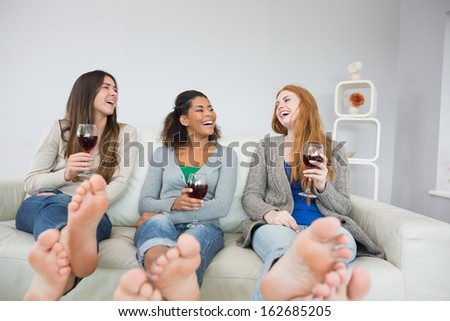 Cheerful young female friends with wine glasses sitting on sofa at home - stock photo