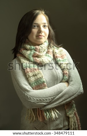 Cheerful young female in winter knitted sweater and scarf posing with arms crossed on dark grey background - stock photo