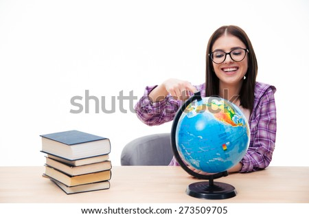 Cheerful young female student sitting at the table and showing finger on globe over white background - stock photo