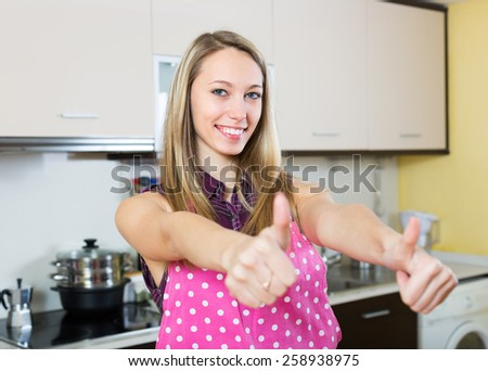 Cheerful young female turned up the thumbs in kitchen  - stock photo
