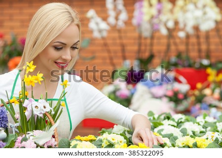 Cheerful young florist is making a bouquet in flower shop. She is holding a basket and choosing some plants from the flowerbed. The woman is smiling - stock photo