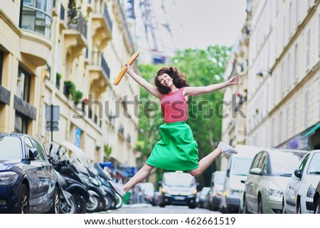 Cheerful young French woman with coffee to go and baguette (white bread) jumping happily on a street of Paris, Eiffel tower in the background
