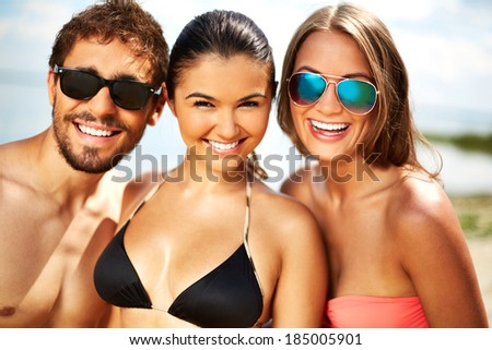 Cheerful young friends looking at camera on the beach - stock photo