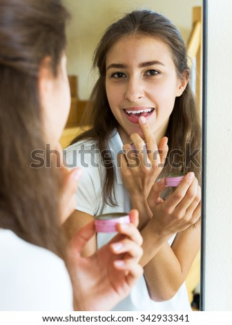 cheerful young girl admiring himself in front of the mirror - stock photo